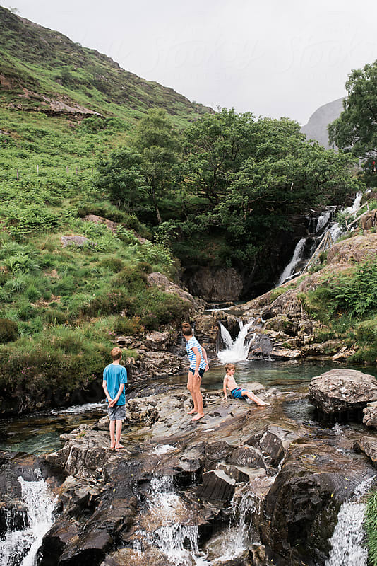 kids playing a water pool in the mountains of Wales by Léa Jones for Stocksy United