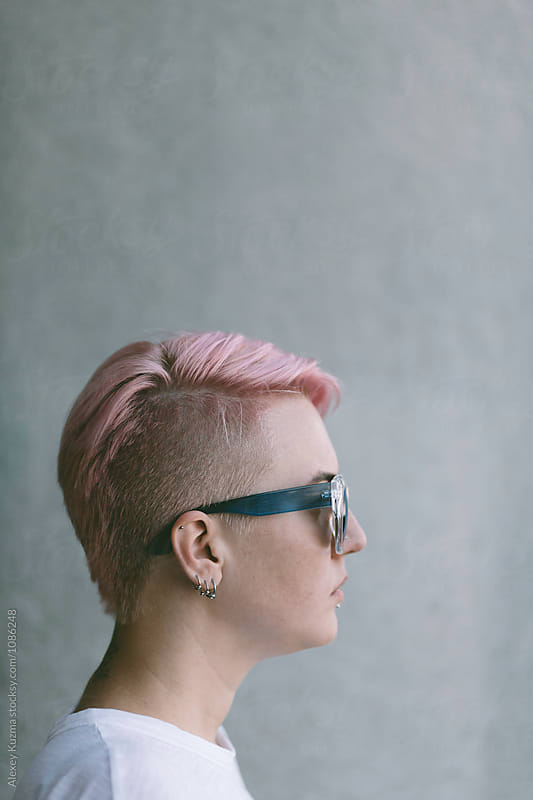 portrait of lesbian woman with pink hair by Alexey Kuzma for Stocksy United