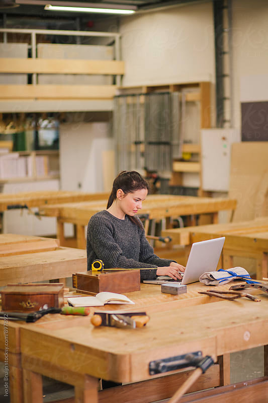 Female woodworker working on a bench surrounded by tools by Ivo de Bruijn for Stocksy United