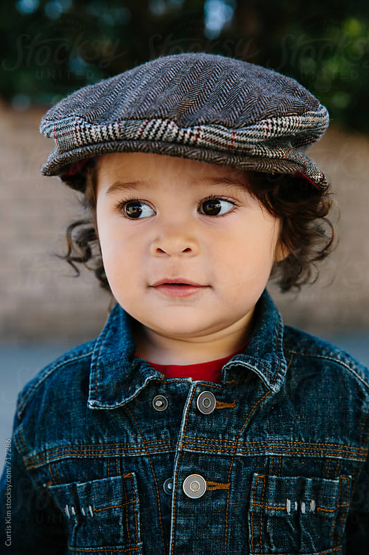 Portrait of a beautiful toddler boy with curly hair by Curtis Kim for Stocksy United