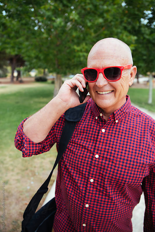 Portrait of smiling elderly man talking over phone in park by Inuk Studio for Stocksy United