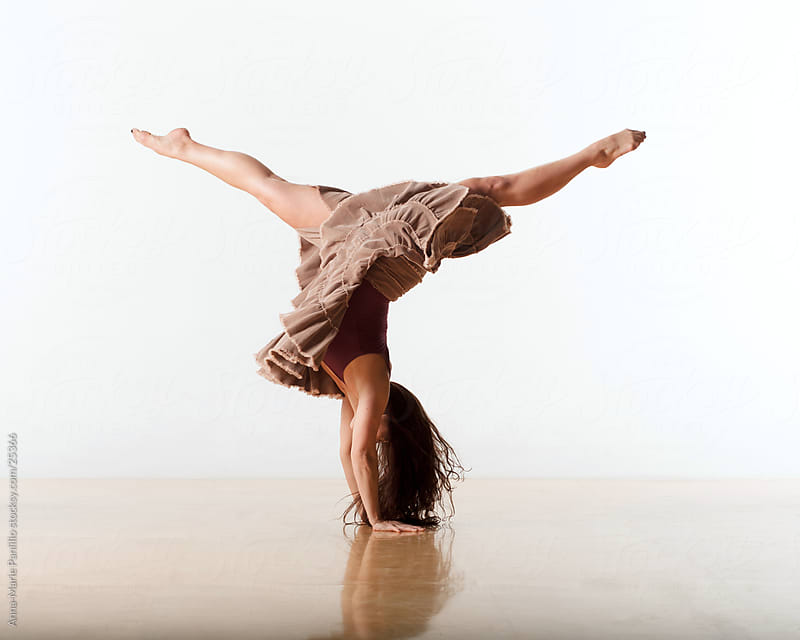 Female dancer gymnast balancing on two hands while doing the splits in the air by Anna-Marie Panlilio for Stocksy United