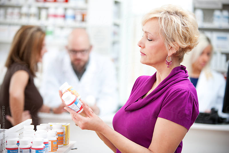 Pharmacy: Woman Shops for Best Medicine Choice by Sean Locke for Stocksy United