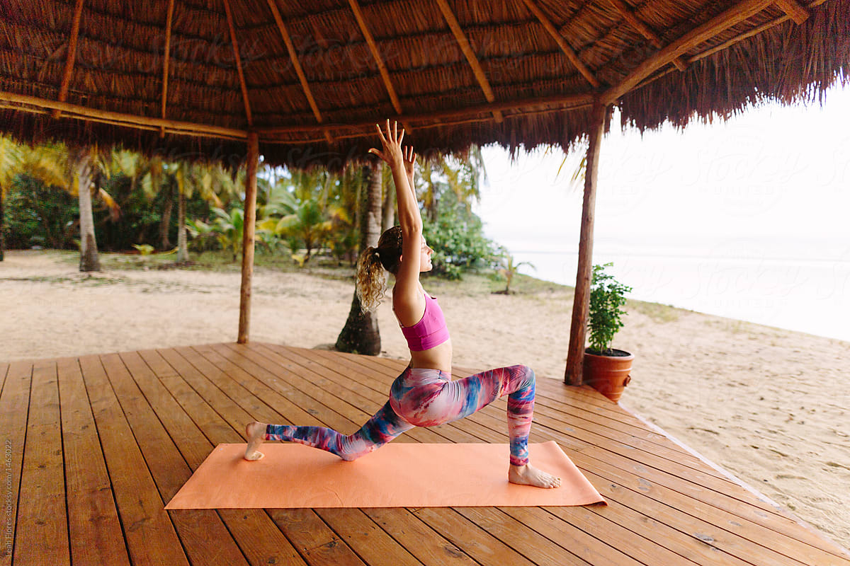 Woman Doing Yoga Poses In Tropical Beach Hut Stocksy United