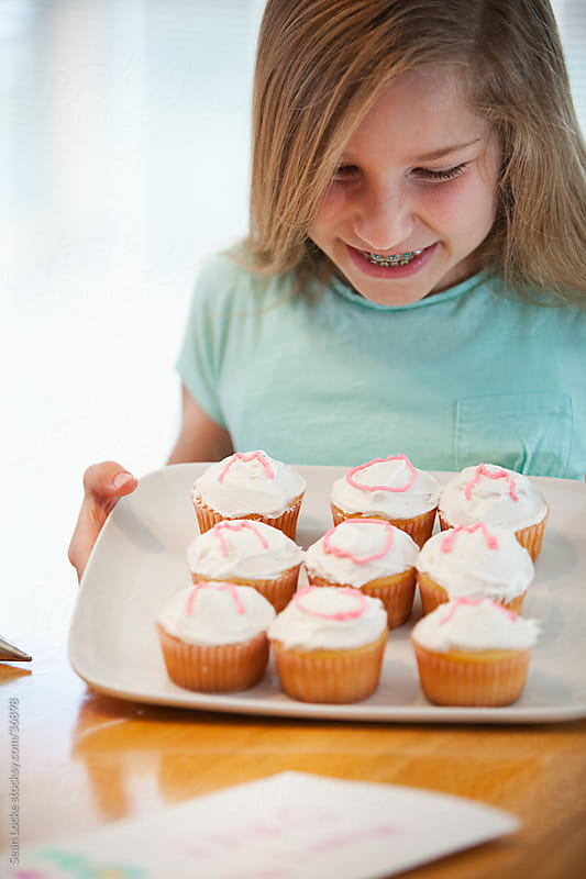 Mother's Day: Girl Happy with Work on Mom's Cupcakes by Sean Locke for Stocksy United