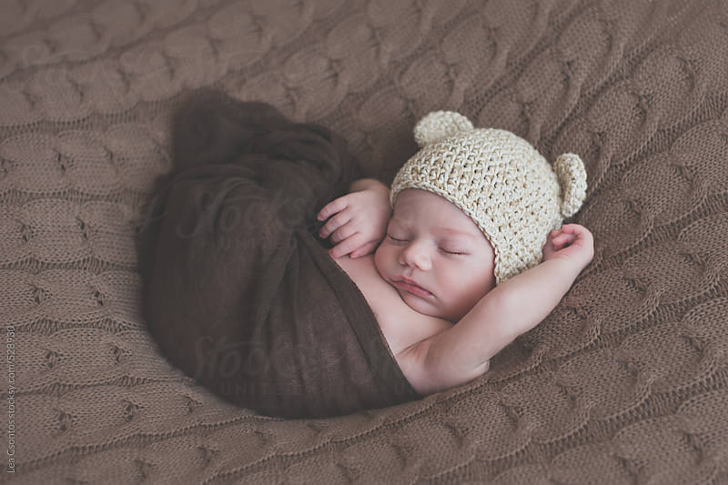 Newborn baby sleeping and snuggling on a blanket wearing a bear hat by Lea Csontos for Stocksy United