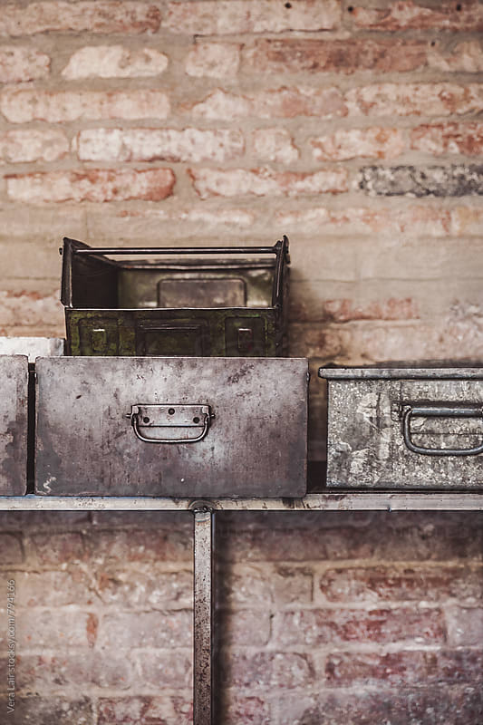 Old rusty containers against of brick grunge wall.  by Vera Lair for Stocksy United