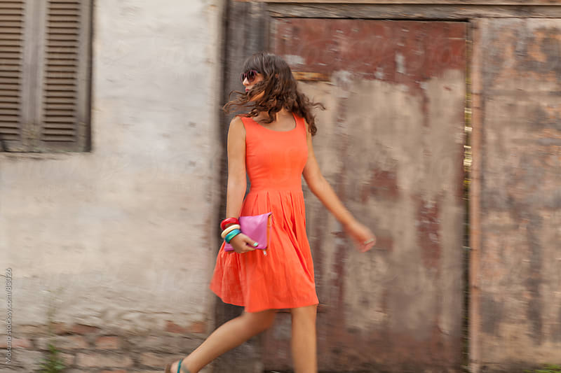 Woman in an orange dress walking down the street. by Mosuno for Stocksy United