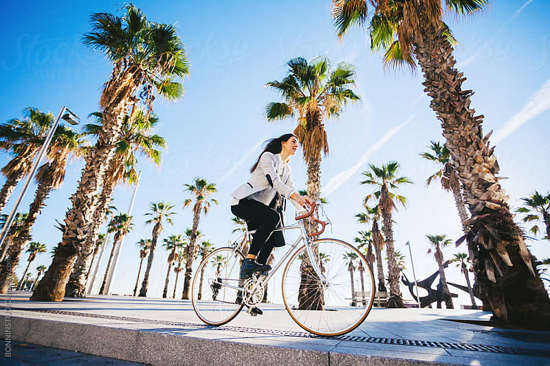Businesswoman riding her vintage bicycle on a beach promenade. by BONNINSTUDIO for Stocksy United