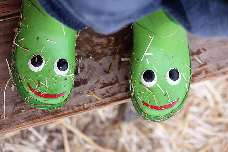 Kiddy rain boots w/ froggy faces on rainy day, standing on a bench by Monica Murphy for Stocksy United