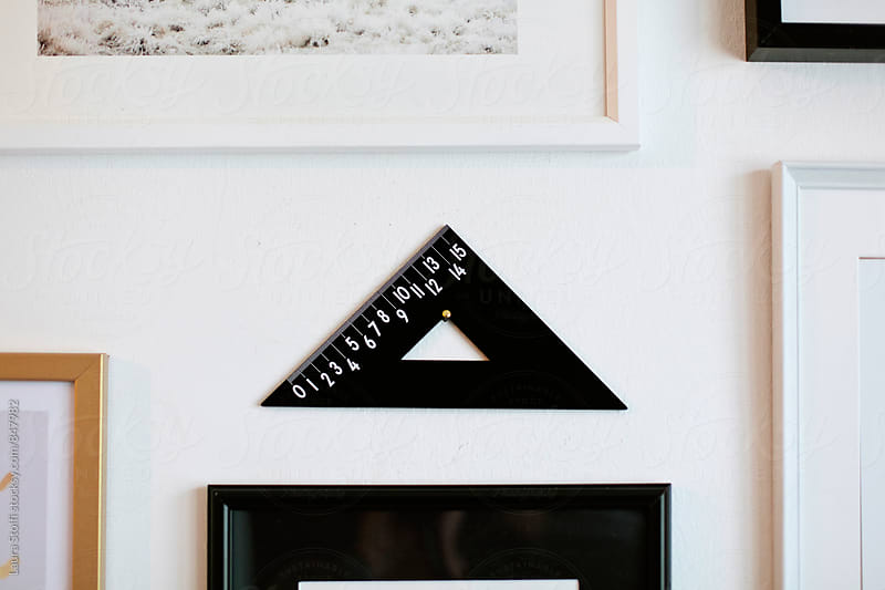 Square ruler used as decor object hanging close to paintings on wall by Laura Stolfi for Stocksy United