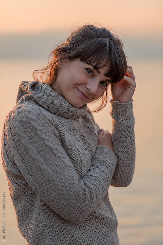 Woman on the beach in winter looking at sunset by Luca Pierro for Stocksy United