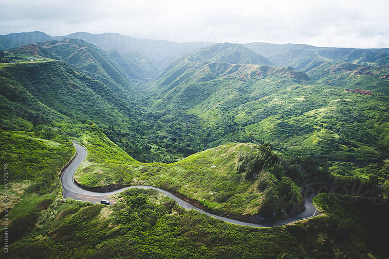 Curving road winding through green mountains with a vehicle parked on the side of the road by Christian Tisdale for Stocksy United