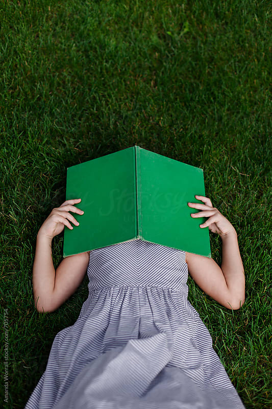 Vertical shot of girl laying in grass with vintage book covering her face by Amanda Worrall for Stocksy United