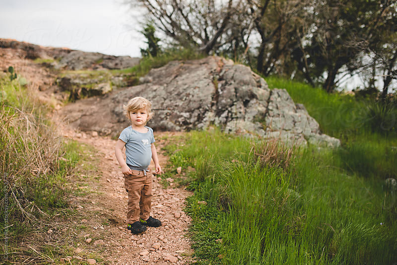 Boy throwing rocks at a park by Courtney Rust for Stocksy United