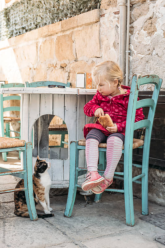 People: Little girl sharing her food with a hungry cat  by Ina Peters for Stocksy United