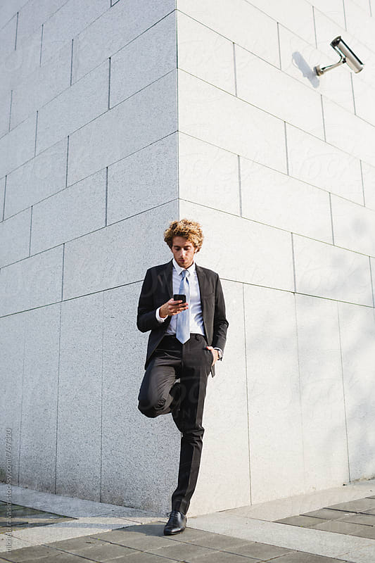 Young man in suit leaning against the wall holding his cell by michela ravasio for Stocksy United