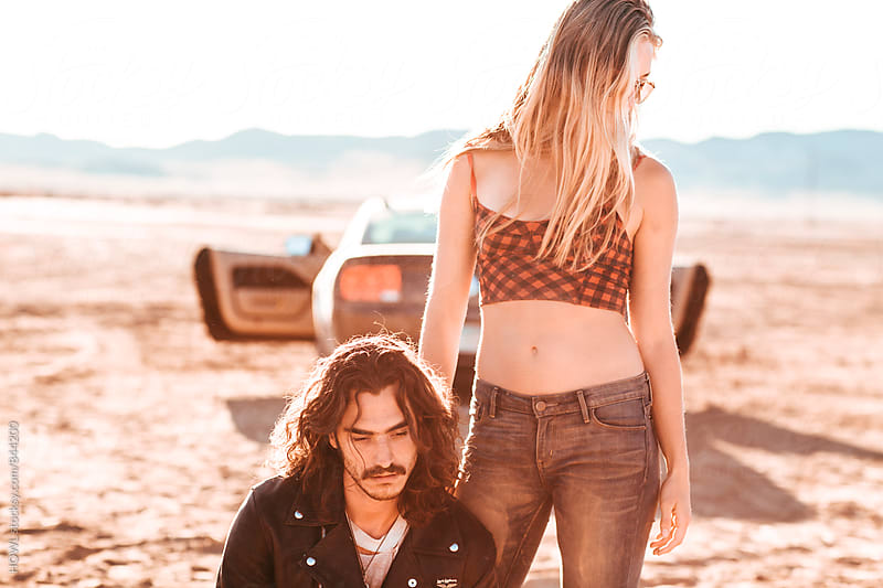 A young couple stands in the middle of the desert looking less than hopeful by HOWL for Stocksy United