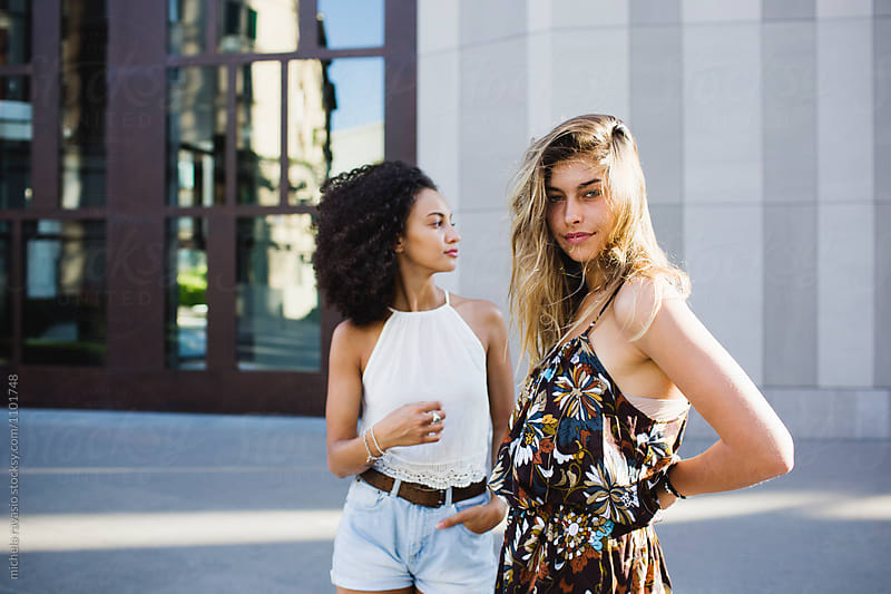 Female friends walking around the city in a summer day. by michela ravasio for Stocksy United