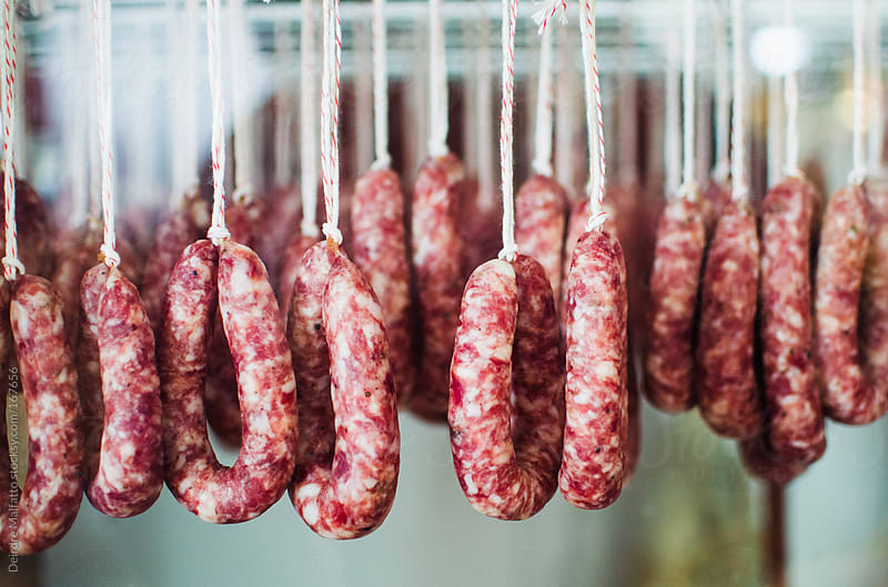 sausages curing and hanging by a string by Deirdre Malfatto for Stocksy United