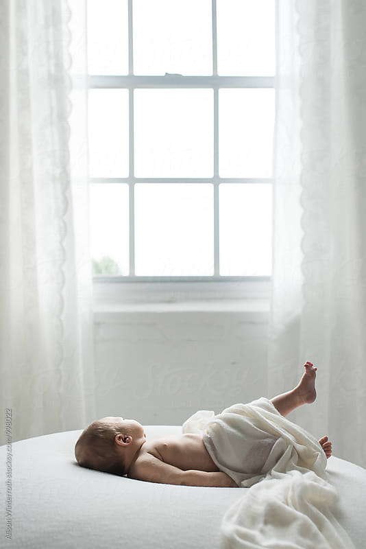 Baby Stretching In Front of Window by Alison Winterroth for Stocksy United