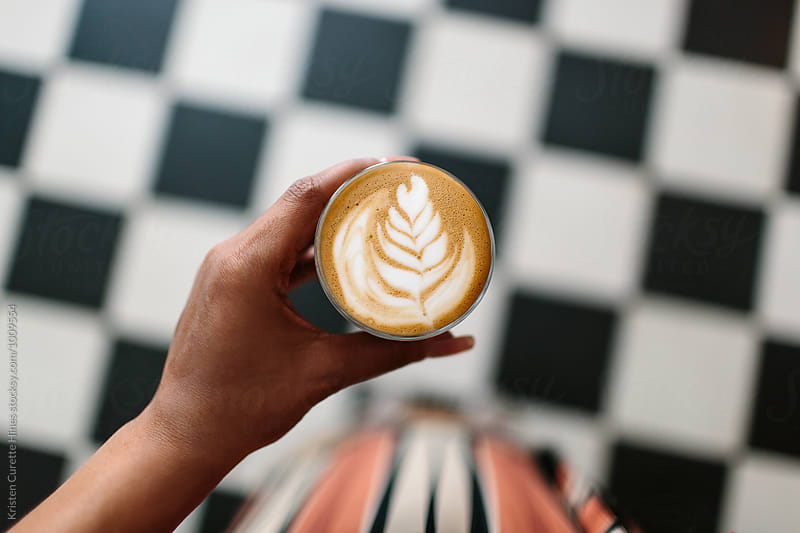 A woman holding a cortado and looking down at a checkered floor.  by Kristen Curette Hines for Stocksy United