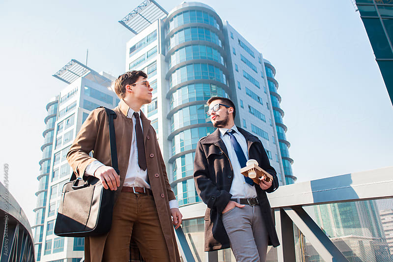 Two successful young men walking and having a chat in front of corporate building.  by Audrey Shtecinjo for Stocksy United