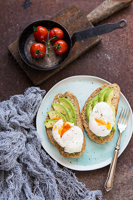 Toast with avocado and poached eggs by Aniko Lueff Takacs for Stocksy United