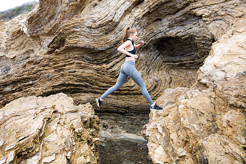 Woman jumping between 2 large rocks by Curtis Kim for Stocksy United
