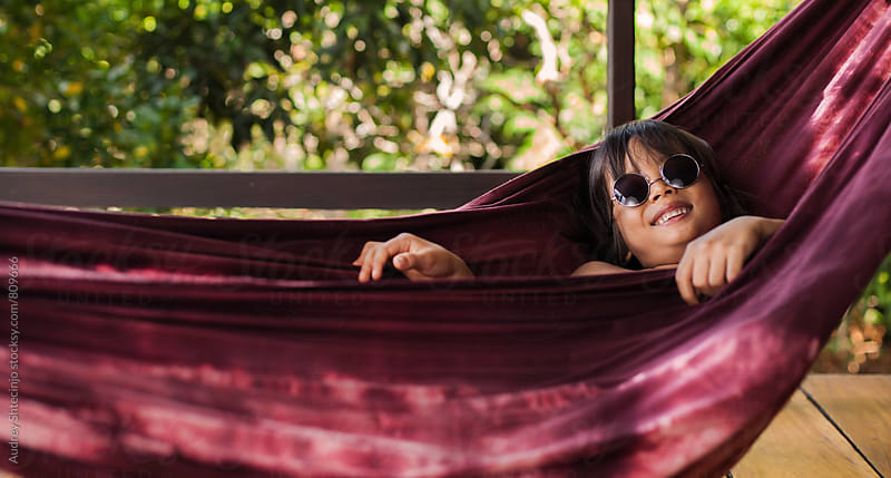 Funny little boy resting in hammock  by Marko Milanovic for Stocksy United