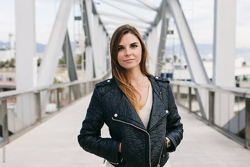 Portrait of a woman wearing a black leather jacket standing on a bridge. by BONNINSTUDIO for Stocksy United
