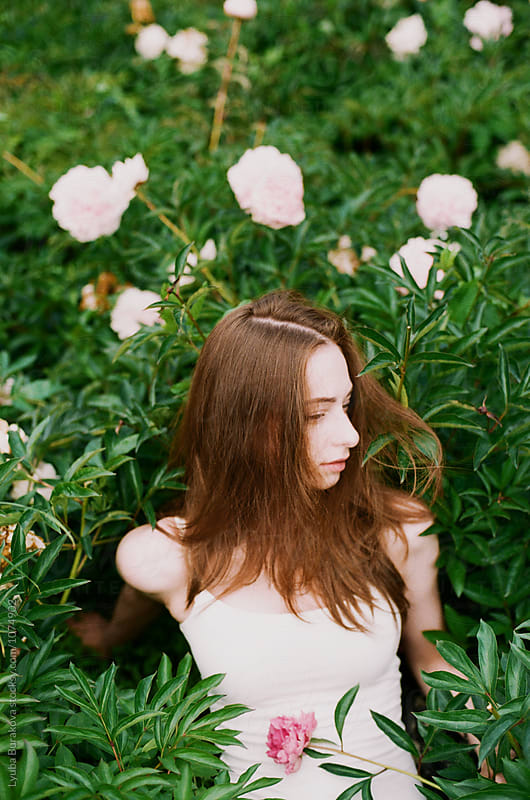 Young woman among peonie by Lyuba Burakova for Stocksy United