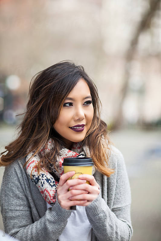 Beautiful Asian woman  holding a coffee cup in an urban area by Suprijono Suharjoto for Stocksy United