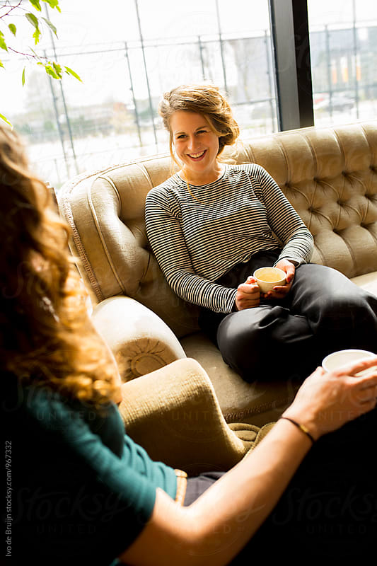 Two young women laughing and drinking coffee, sitting on a couch. by Ivo de Bruijn for Stocksy United