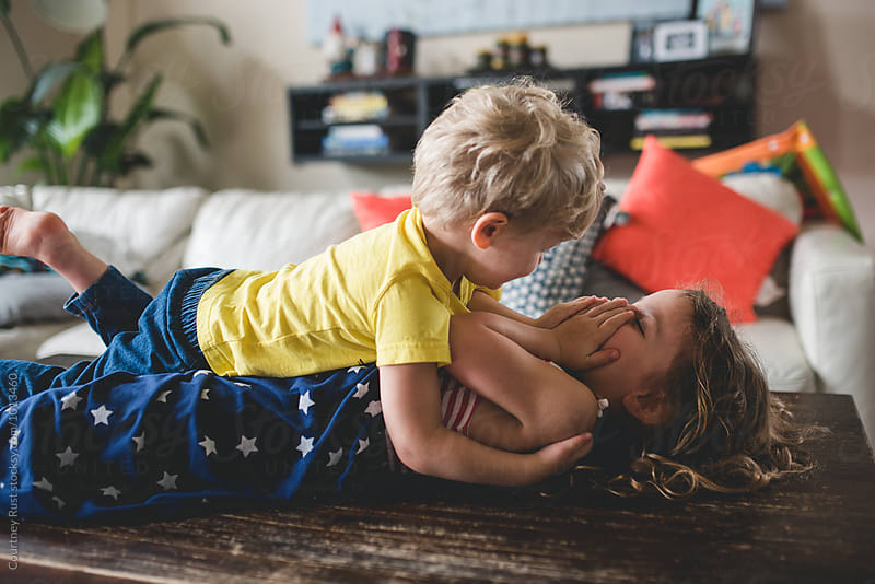 siblings hugging and wrestling on coffee table by Courtney Rust for Stocksy United