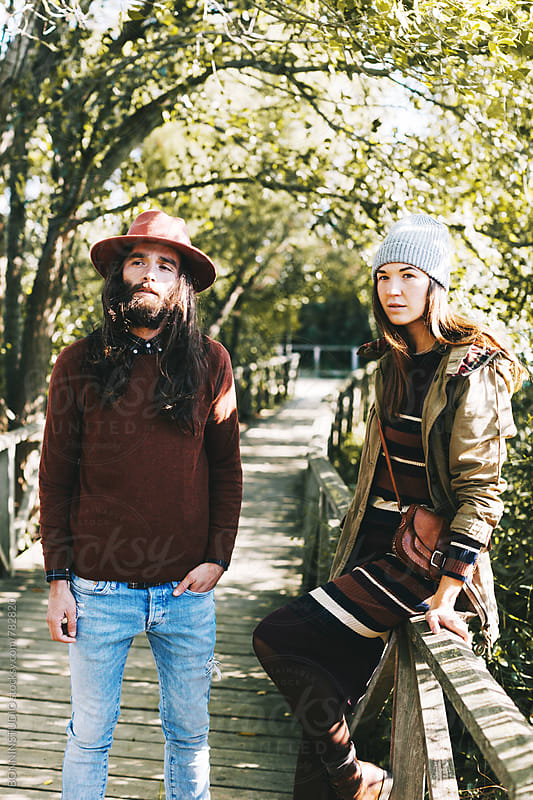 Young hipster couple standing on a wooden bridge in the forest. by BONNINSTUDIO for Stocksy United