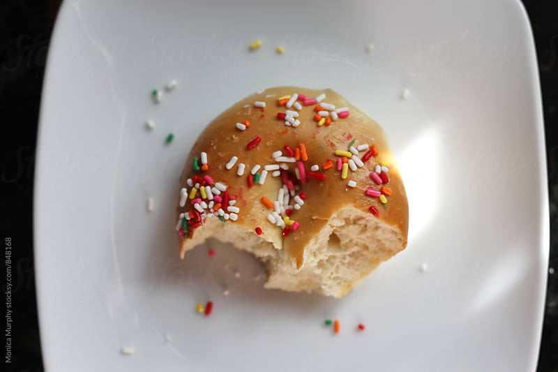 Sprinkle covered bagel with bites taken  by Monica Murphy for Stocksy United