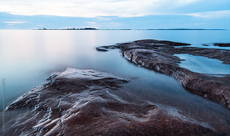 The blue hour on the rocky shore by Jonatan Hedberg for Stocksy United