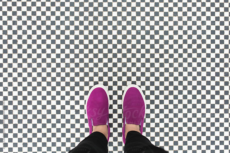Hot pink sneakers on checkerboard tile by Amy Covington for Stocksy United