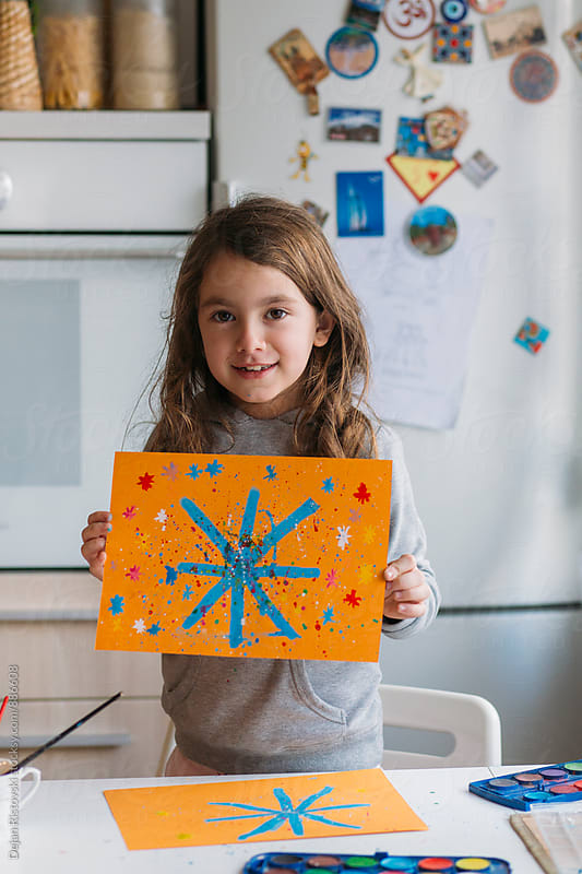 Little girl showing painting. by Dejan Ristovski for Stocksy United