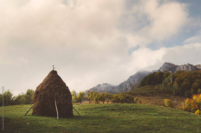 Rural mountain landscape with haystack by Cosma Andrei for Stocksy United