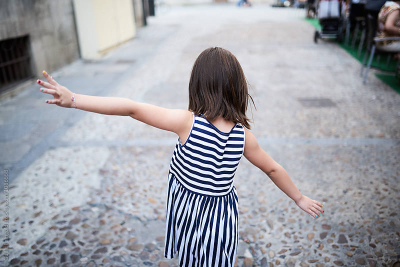 Brunette kid in striped dress with outstretched arms walking along road by Guille Faingold for Stocksy United