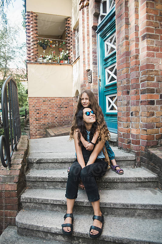 Mother and her long haired 6 years old daughter on their front porch by Irina Efremova for Stocksy United