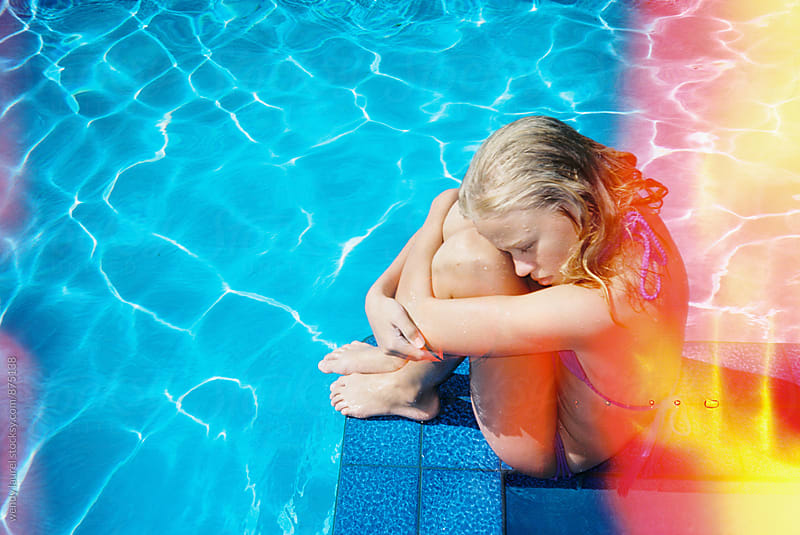 girl holding herself in pool with light leak by wendy laurel for Stocksy United