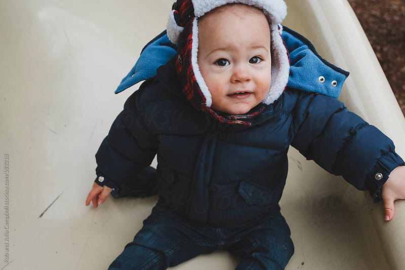Little boy smiling on playground slide in winter by Rob and Julia Campbell for Stocksy United