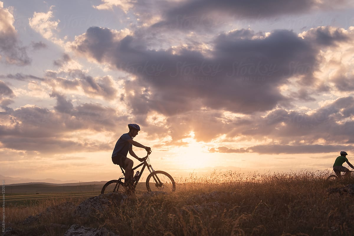 Young man on bike riding MTB across a green field during sunset by ...