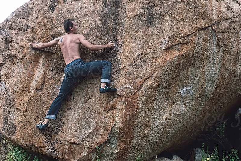 Young muscular man bouldering on a rock face  by RG&B Images for Stocksy United