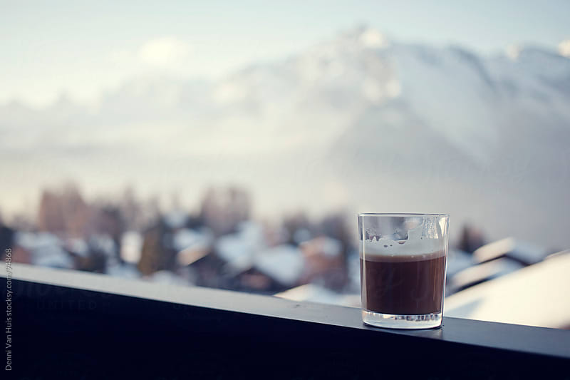 A hot beverage on the railing of a chalet by Denni Van Huis for Stocksy United