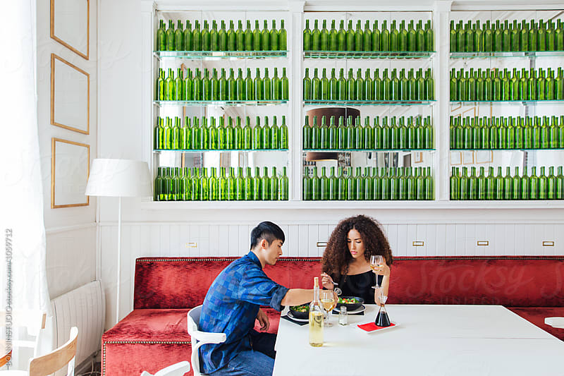 Multi-ethnic couple eating a healthy meal in a cool restaurant.  by BONNINSTUDIO for Stocksy United