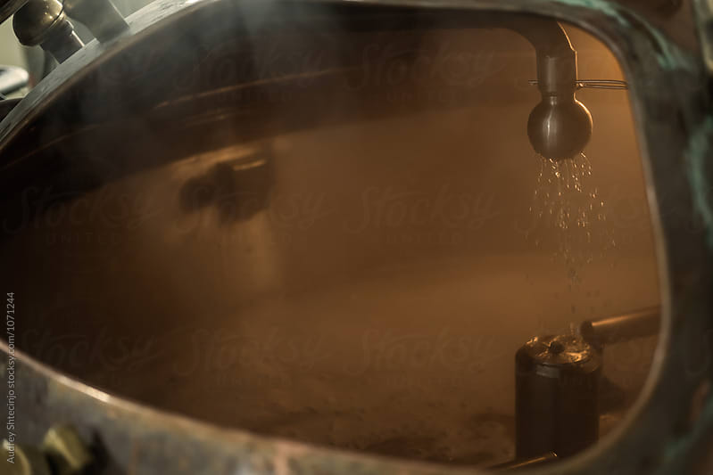 Process of mixing water  with ingredients in distillery tank by Marko Milanovic for Stocksy United